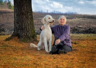 Golden doodle and smiling elderly woman sitting in pine needles with big blue sky - Fetching Foto Photography, Chicagoland-IL